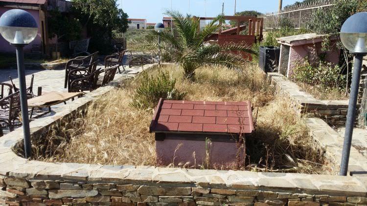 giardino con erbacce prima della pulizia e posatura del prato sintetico