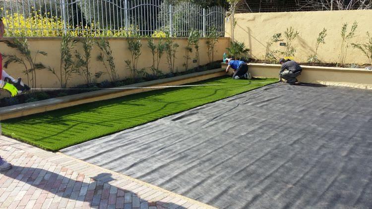 posa del prato in erba artificiale nel giardino privato, Sassari